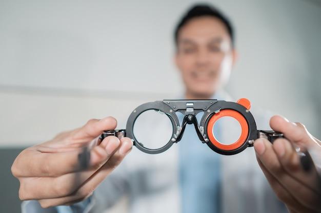 Een mannelijke arts die een oogtest meethulpmiddel in een oogkliniek met de doktersmuur houdt