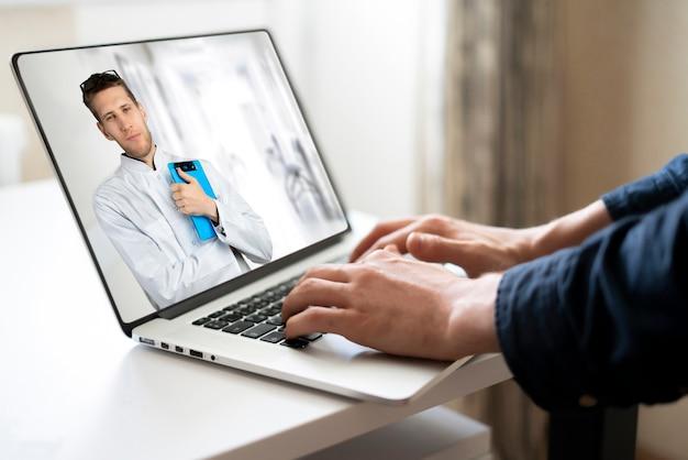 Een mannelijke arts die onderzoek doet op de webcam van een laptop, belt online naar de patiënt thuis