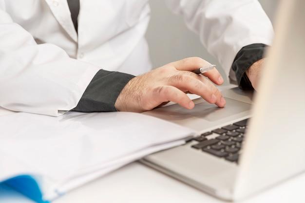 Een mannelijke arts in een witte jas vult een medische geschiedenis op een laptop. detailopname.
