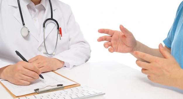 Een mannelijke arts in overleg met een patiënt.