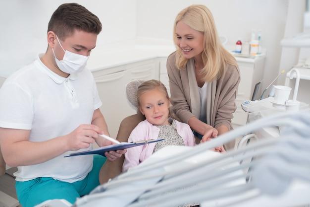 Een mannelijke arts legt de röntgenresultaten uit aan de moeder van de kinderen