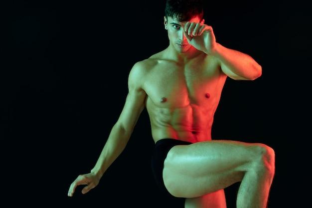 Een mannelijke atleet met een opgepompte romp hief zijn been op op een zwarte achtergrond en gebaren met zijn handen kopieer ruimte