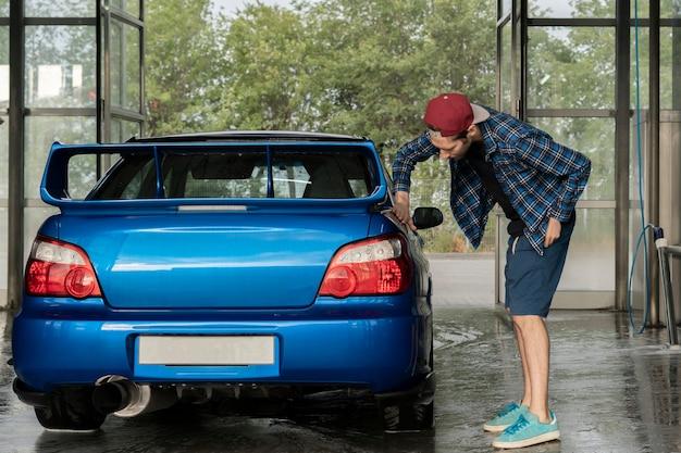 Een mannelijke bestuurder die de auto in de doos van het zelfwasstation schoonmaakt