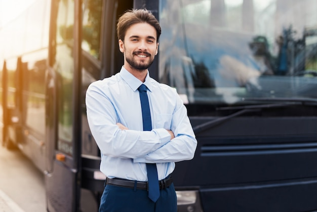Een mannelijke bestuurder die en tegen een zwarte toeristenbus glimlacht stelt