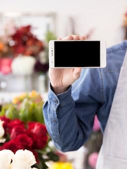 Een mannelijke bloemist die weergavescherm van mobiele telefoon in de bloemwinkel toont