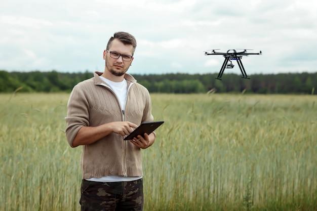 Een mannelijke boer beheert een drone over landbouwgrond.