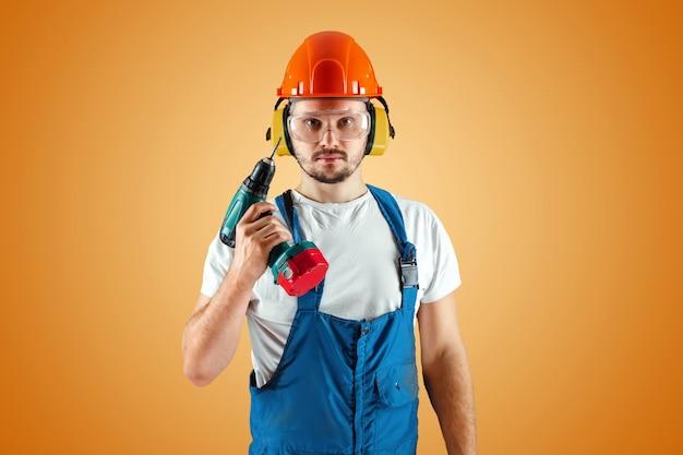 Een mannelijke bouwvakker in een oranje helm houdt een schroevendraaier op een oranje achtergrond.