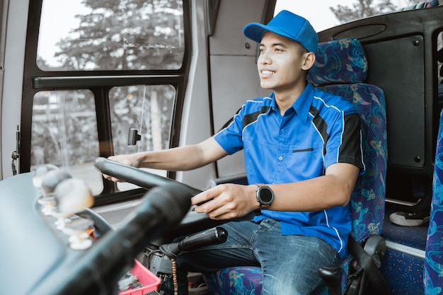 Een mannelijke buschauffeur in blauw uniform rijdt de bus