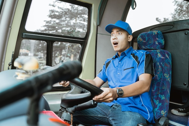 Een mannelijke buschauffeur in blauw uniform wordt geschokt tijdens het besturen van de bus