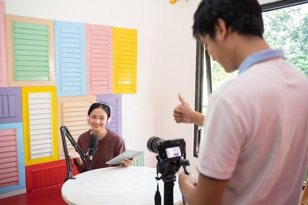 Een mannelijke cameraman met een duim omhoog teken klaar om te beginnen met opnemen met een camera naar een meisje dat een hoofddoek draagt...