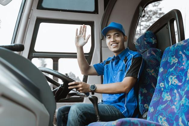 Een mannelijke chauffeur in uniform glimlacht naar de camera terwijl hij gaat zitten en zwaait naar de bus