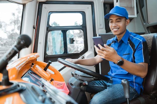 Een mannelijke chauffeur in uniform kijkt naar zijn mobiel terwijl hij het stuur in de bus vasthoudt