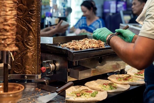 Een mannelijke chef-kok bereidt een vleesshoarma op straat, hij stopt gebakken vlees in tortilla's, de koks gehandschoende ...