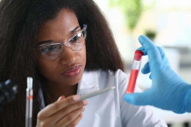 Een mannelijke chemicus houdt reageerbuis glas vast