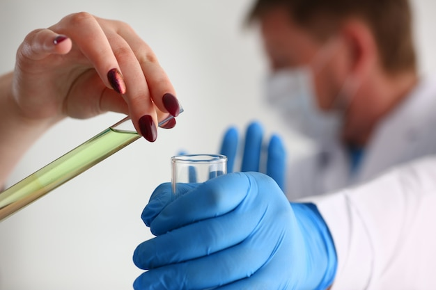 Een mannelijke chemicus houdt reageerbuis van glas in zijn hand overloopt een vloeistof