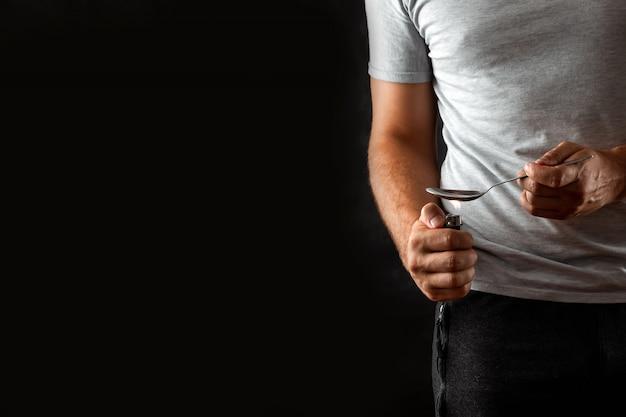 Een mannelijke drugsverslaafde bereidt medicijnen in een lepel met een aansteker