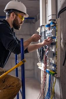 Een mannelijke elektricien werkt in een schakelbord met een elektrische verbindingskabel