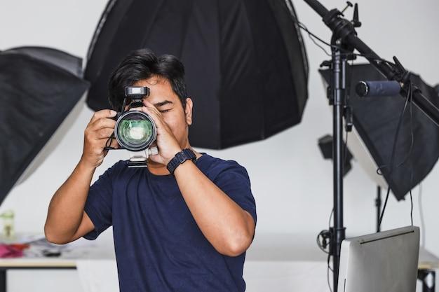 Een mannelijke fotograaf maakt foto's met een reeks lichten op de achtergrond