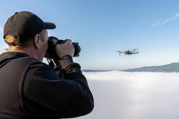 Een mannelijke fotograaf maakt foto's van een drone die in een dikke mist in de lucht boven de top van een ...