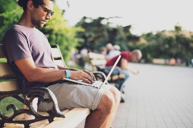 Een mannelijke freelancer die op straat werkt met de laptop