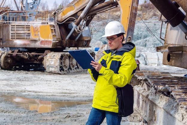 Een mannelijke geoloog of een mijningenieur schrijft iets in een kaartdoos te midden van een steengroeve met bouwmachines