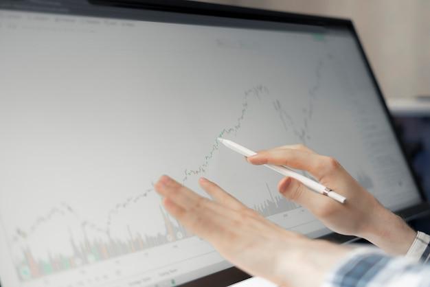 Een mannelijke handelaar die thuis de aandelengrafiek op een groot computerscherm bekijkt, grafiekanalyse