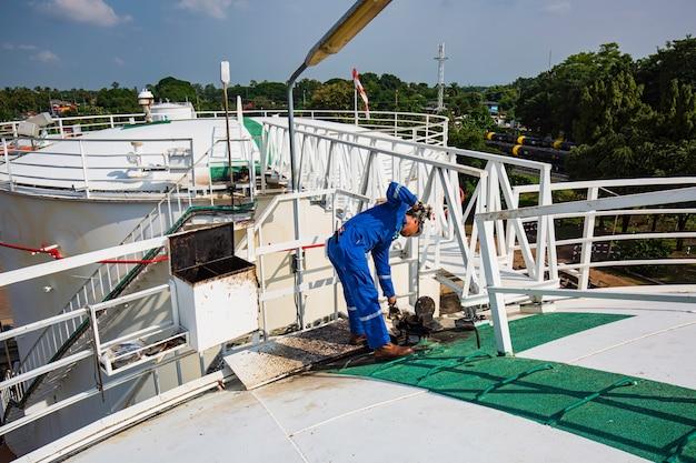 Een mannelijke industriële ingenieurs inspectieniveau stookolietank in chemische fabriek