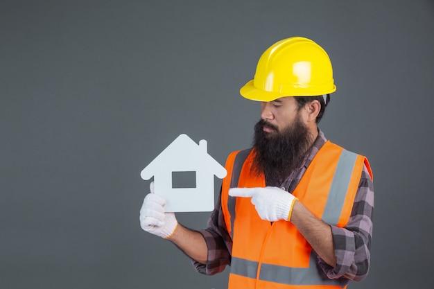 Een mannelijke ingenieur die een gele veiligheidshelm draagt die een wit huissymbool op grijs houdt.