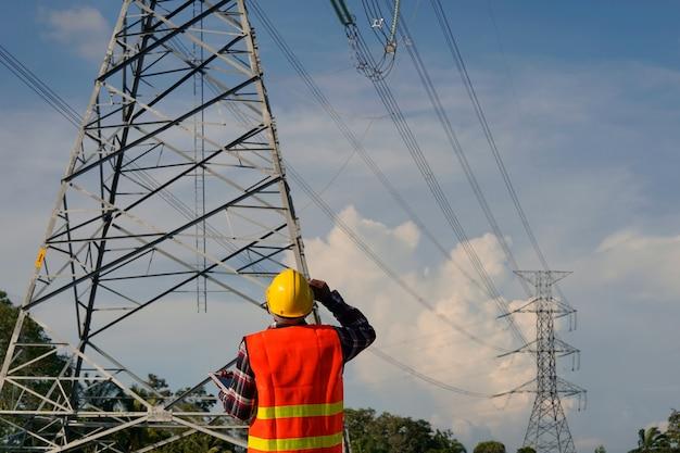Een mannelijke ingenieur gebruikt een laptop en inspecteert de bouwwerkzaamheden. een grote elektriciteitspaal voor de bouwplaats.