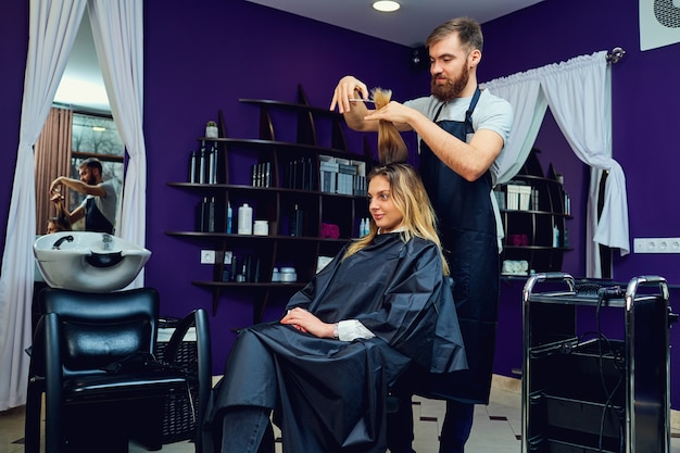 Een mannelijke kapper doet een kapsel voor een vrouw in de schoonheidssalon van het haar.