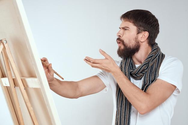 Een mannelijke kunstenaar tekent op een ezel een sjaal wit t-shirt
