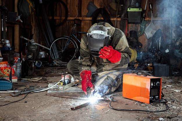 Een mannelijke lasser in een lasmasker werkt met een boogelektrode in zijn garage. lassen, constructie, metaalbewerking.