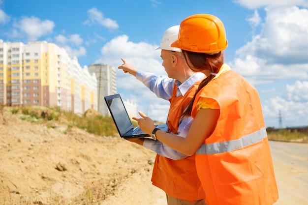 Een mannelijke manager op een bouwplaats die een harde hoed draagt en met zijn vrouwelijke collega praat en thuis wijst
