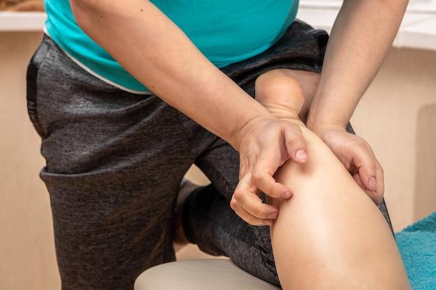 Een mannelijke masseur laat voeten en benen met zijn handen masseren tot een concept voor vrouw, voetverzorging en wellness