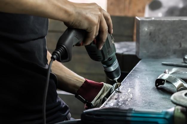 Een mannelijke metaalarbeider droeg een stuk middeleeuws pantserkostuum. man handen behandelen van metalen onderdelen van hardware in een workshop met elektrische boormachine