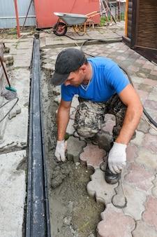 Een mannelijke metselaar maakt een pad uit straatstenen