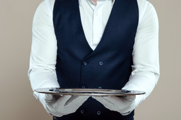 Een mannelijke ober in een wit overhemd en witte handschoenen staat met een zilveren dienblad. het concept van servicepersoneel dat klanten in een restaurant bedient.