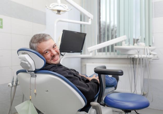 Een mannelijke patiënt zit in de stoel van de tandarts en glimlacht. moderne technologieën in tandheelkundige behandelingen