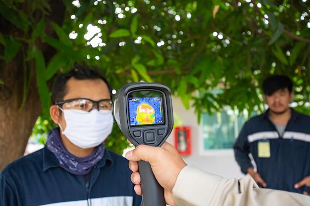 Een mannelijke persoon die wordt gemeten, scant de lichaamstemperatuur met een contactloze infrarood