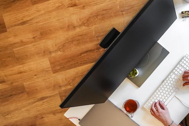 Een mannelijke programmeur werkt voor een laptopscherm in een helder kantoor of op afstand van huis