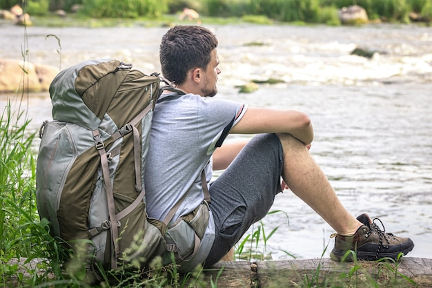 Een mannelijke reiziger met een grote wandelrugzak zit bij de rivier te rusten.