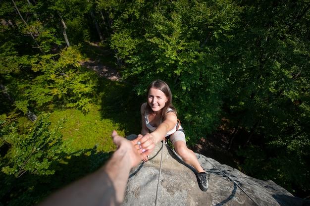 Een mannelijke rockclimber die aan glimlachende vrouwelijke klimmer helpt om een piek van berg te bereiken