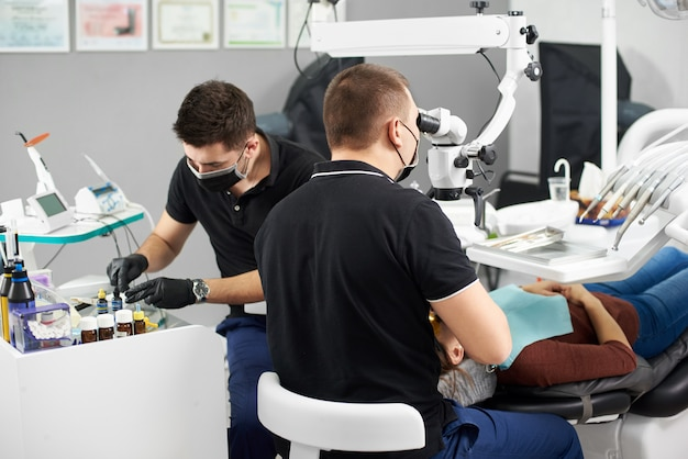 Een mannelijke tandarts maakt de tanden van een patiënt vast terwijl een andere mannelijke tandarts de tandvulling voorbereidt