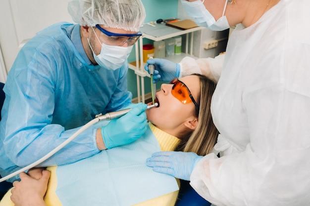 Een mannelijke tandarts met tandheelkundige hulpmiddelen boort de tanden van een patiënt met een assistent. het concept van geneeskunde, tandheelkunde en gezondheidszorg.