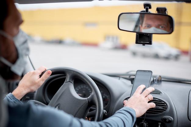 Een mannelijke taxichauffeur met een medisch masker stapt in de auto en zet de navigator aan op zijn smartphone