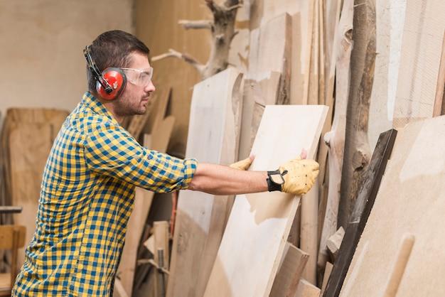 Een mannelijke timmerman die beschermende veiligheidsbril draagt die houten plank in de workshop houdt