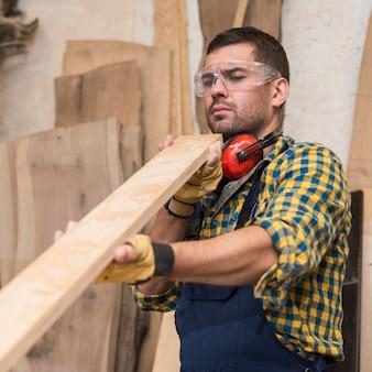 Een mannelijke timmerman die ernstig houten plank bekijkt