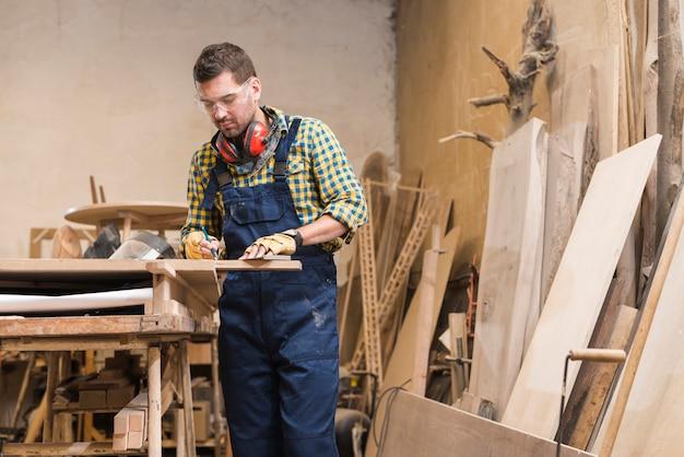 Een mannelijke timmerman die in de workshop werkt