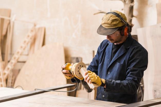 Een mannelijke timmerman die met orbitale schuurmachine voor het vormen van houten blok werkt