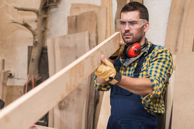 Een mannelijke timmerman die veiligheidsbril draagt die houten plank bekijkt